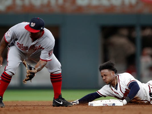 Atlanta Braves' Ozzie Albies is safe at second base with a double as Washington Nationals second baseman Howie Kendrick waits for the throw during the fifth inning of a baseball game Tuesday, April 3, 2018, in Atlanta. (AP Photo/John Bazemore)