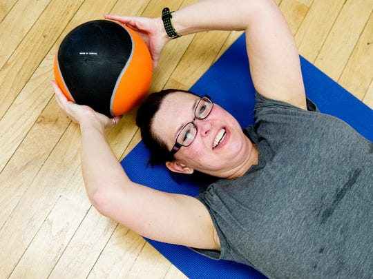 Sharon Pooley does an exercise with a medicine ball during her New U fitness training class at Fort Sanders Health and Fitness on Thursday, March 16, 2017, in Knoxville. Pooley has overcome breast cancer and uterine cancer and is part of the New U Challenge health and fitness program and will run in the Covenant Health Knoxville Marathon's half marathon on April 2.