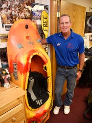Rick Rassier stands next to a kayak in his St. Cloud