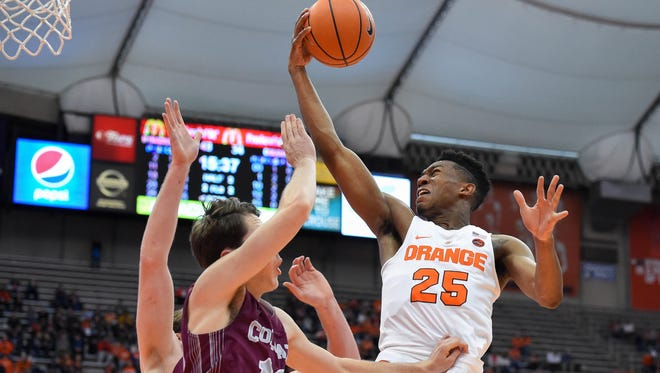 Syracuse Orange guard Tyus Battle (25) drives to the basket for a shot over Colgate Raiders guard Jack Ferguson (13) during the second half at the Carrier Dome.