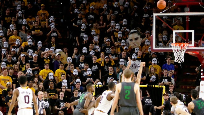 Arizona State students wear masks during an NCAA college basketball game against Oregon, Sunday, Jan. 31, 2016, in Tempe, Ariz. Oregon defeated Arizona State 91-74. (AP Photo/Rick Scuteri)