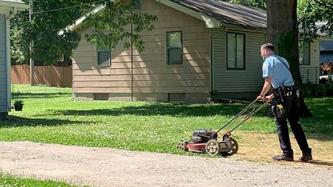 Sgt. Sean Swisshelm mows the lawn of a Leavenworth resident who is suffering mental health issues.