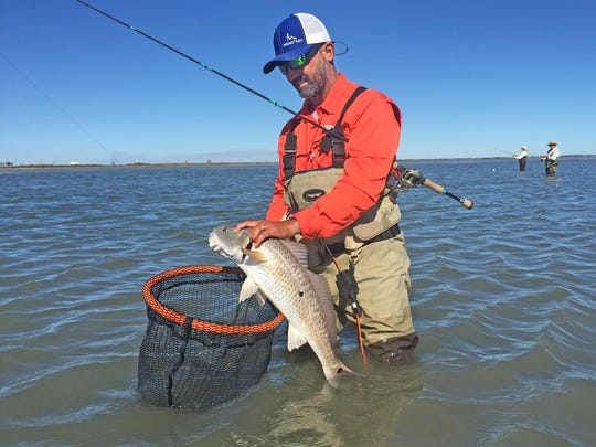 The pair of anglers in the background were generous enough to allow us to share a productive spot with them on the backside of Mustang Island. That Javi Castillo with the redfish.