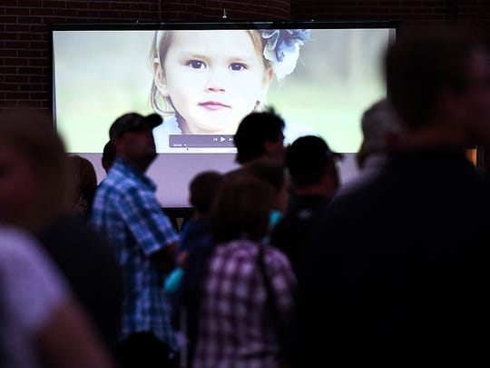 A large photo of Alayna Ertl, 5, was projected on a screen Tuesday before the start of a candlelight vigil at St. Anthony Catholic Church in Watkins.