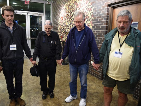 Room in the Inn founder Charles Strobel, center, prays with volunteers and staff before opening the doors to the Nashville homeless shelter.