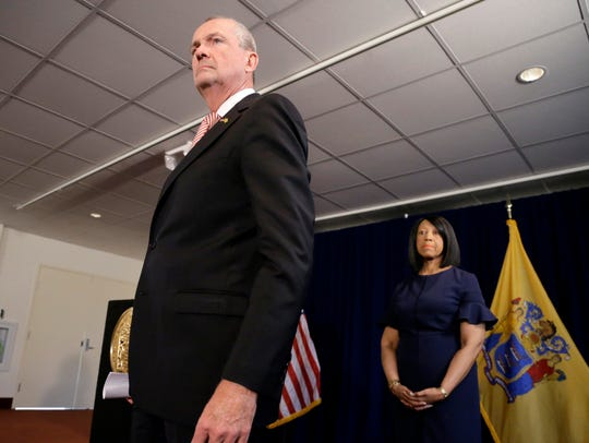 New Jersey Gov. Phil Murphy, left, steps forward to