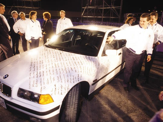 BMW employees sign their name on the first car assembled at the BMW plant in Spartanburg, South Carolina, a 318i, in September 1994.