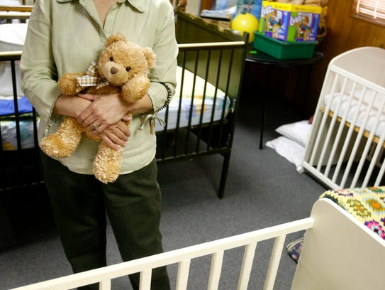 Clutching a teddy bear left behind at a shelter used