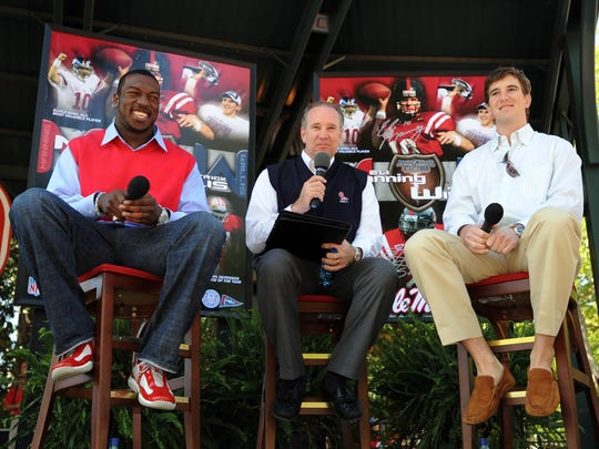"""Former Ole Miss Rebel Patrick Willis, left, and Eli Manning, right, answer questions from """"Voice of the Rebels"""" David Kellum  in The Grove at the University of Mississippi during a special presentation before the Rebels Spring game."""