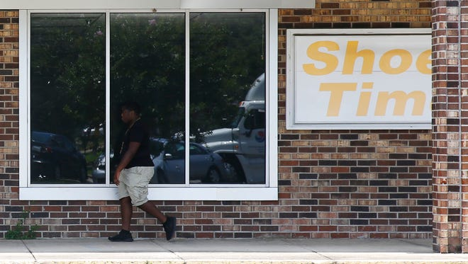 A Tallahassee resident walks past the structural remains of an abandoned Shoe! Time shop on South Monroe Street.