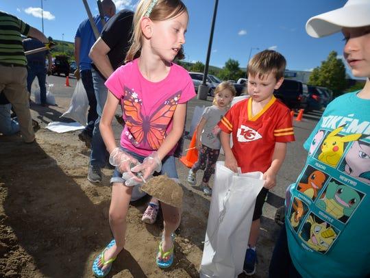 Madison Olsen, age 7, fills up a sandbag with Carter