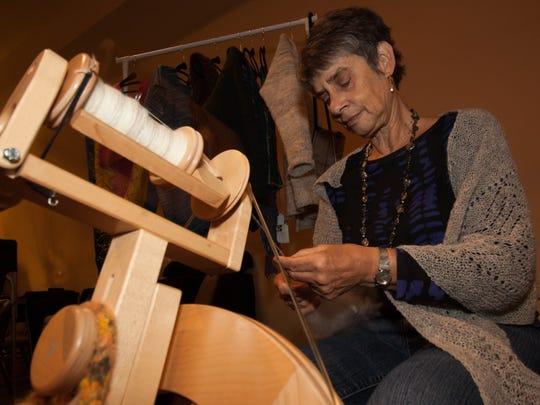 Fiber Artist Carol Eggers spins fleece from a sheep on her spinning wheel.
