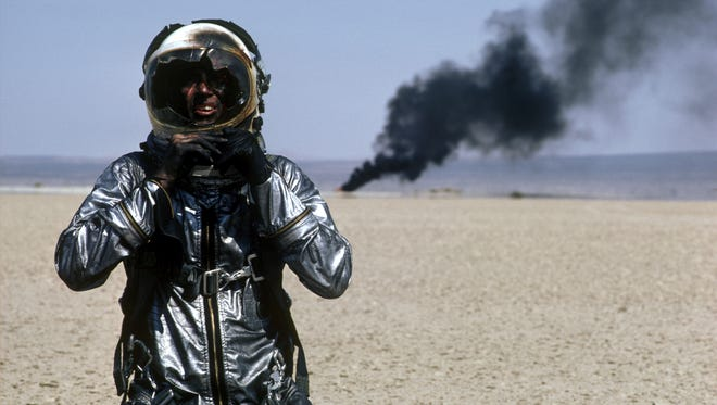 Sam Shepard as Chuck Yeager, wearing flight suit and helmet; burning wreckage in background.