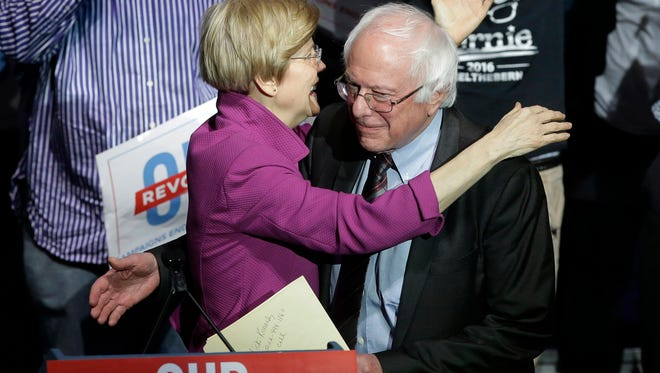 Sens.s Elizabeth Warren, D-Mass., left, and Bernie Sanders, I-Vt., right, embrace during a rally Friday, March 31, 2017, in Boston. Sanders and Warren are making a joint appearance at the evening rally in Boston as liberals continue to mobilize against the agenda of Republican President Donald Trump. (AP Photo/Steven Senne)
