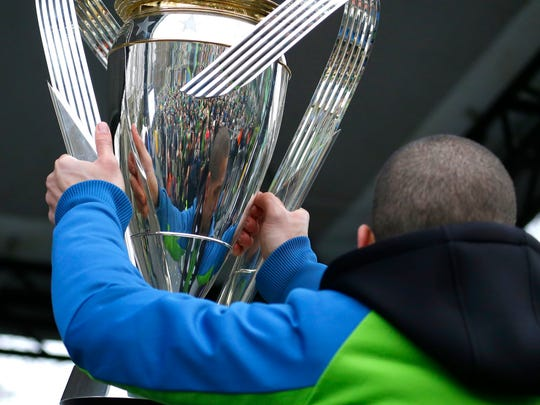 Seattle Sounders midfielder and captain Osvaldo Alonso is reflected in the MLS Cup trophy as he holds up for the crowd during a championship rally Tuesday in Seattle.