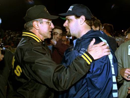 Mike Pettine Sr. (left) greets his son, then head coach at North Penn High School, following their second 1999 meeting, in the state playoffs. Pettine Sr.'s team would go on to capture the state title in his final year as C.B. West head coach. That year, both Pettines were featured in season-long documentaries, The Last Game and The Season.