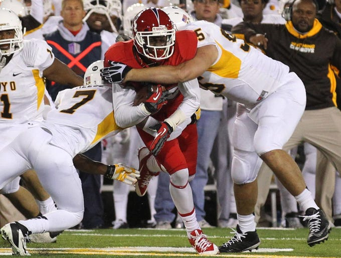 Fresno State wide receiver Davante Adams is tackled by Wyoming safety Chad Reese and nose guard Patrick Mertens during the first quarter at War Memorial Stadium.