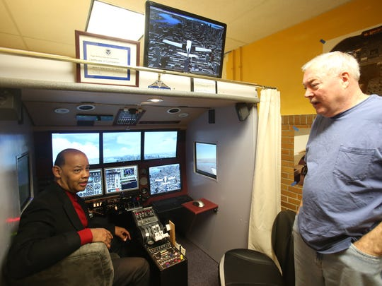 From left, Frank Williams of Youth Bureau talks with pilot James Parker who donated a flight simulator to the White Plains Youth Bureau in White Plains Jan. 2, 2018.