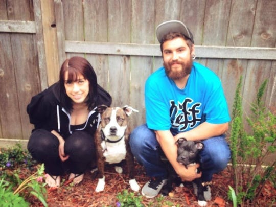 Brittany Dahlke and her boyfriend, Alex Perez, pose with their pit bull-mixes that Dahlke says are non-aggressive.