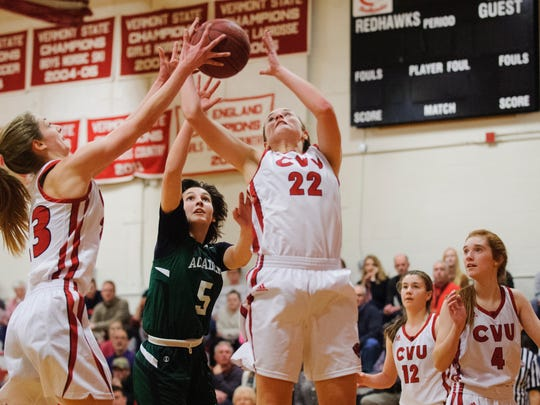 CVU's Lindsey Albertelli (22) leaps over St. Johnsbury's Sadie Stetson (5) to grab the rebound during the girls basketball game between the St. Johnsbury Hilltoppers and the Champlain Valley Union Redhawks at CVU High School on Tuesday night January 9, 2018 in Hinesburg.