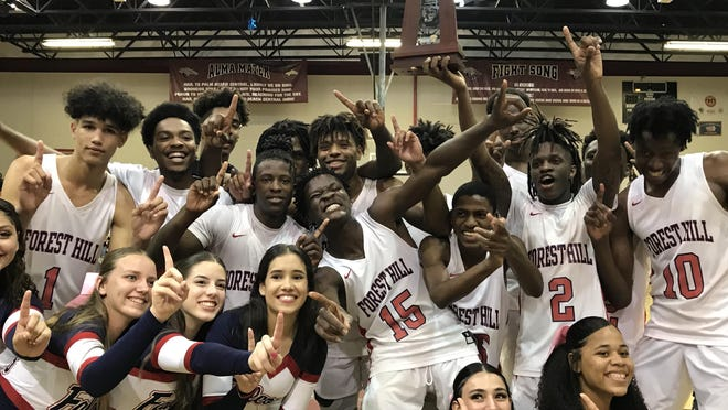 The Forest Hill boys basketball team celebrates its 77-52 win over Wellington in Friday night's Class 7A District 10 final at Palm Beach Central. It was Forest Hill's second consecutive district title.