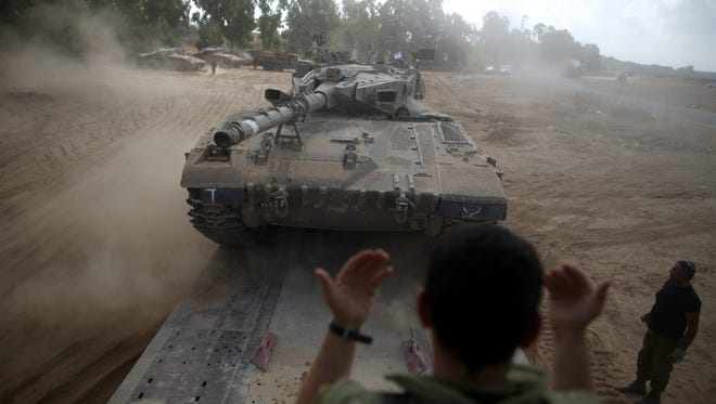An Israeli soldier directs a Merkava tank being loaded on  a carrier truck at an unspecified location near the Israeli border with Gaza on Aug. 6.