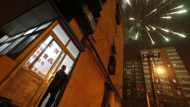 A Chinese man stands at the building entrance of his home as fireworks explode in the sky minutes after midnight in Beijing on Jan. 24.