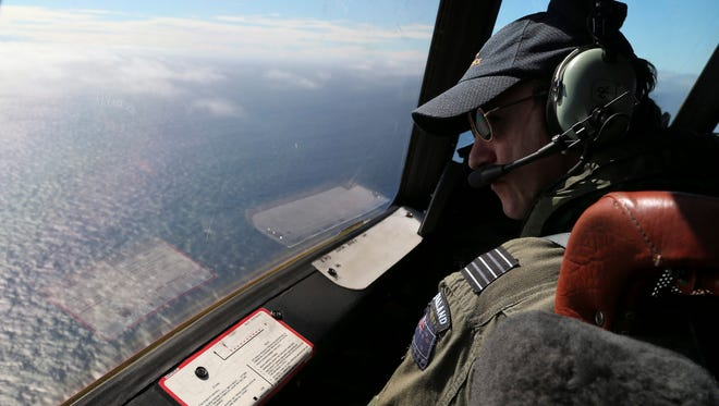 Royal New Zealand Air Force Wing Commander Rob Shearer's looks out of the window of his P-3 Orion aircraft while searching for missing Malaysia Airlines Flight MH370, off Perth, Australia, on Monday.