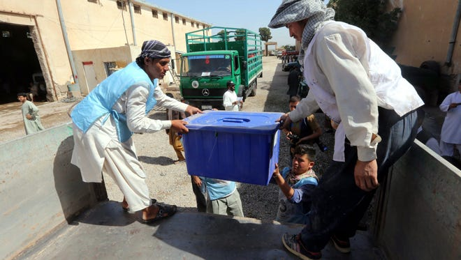 Afghan workers load electoral materials on a truck to be sent to polling station in Herat, Afghanistan, on June 11.
