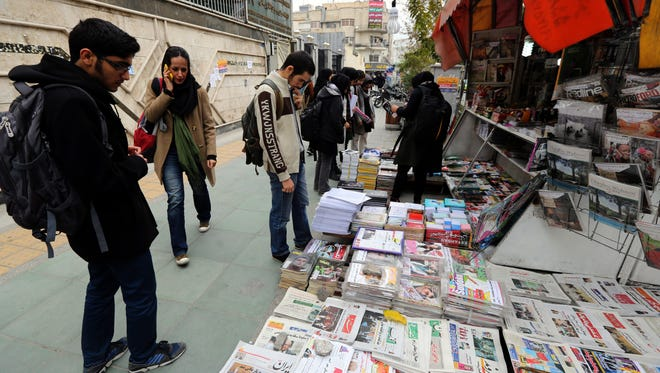 Iranians look at newspapers displayed on the ground outside a kiosk in a street of Tehran on Nov. 24.