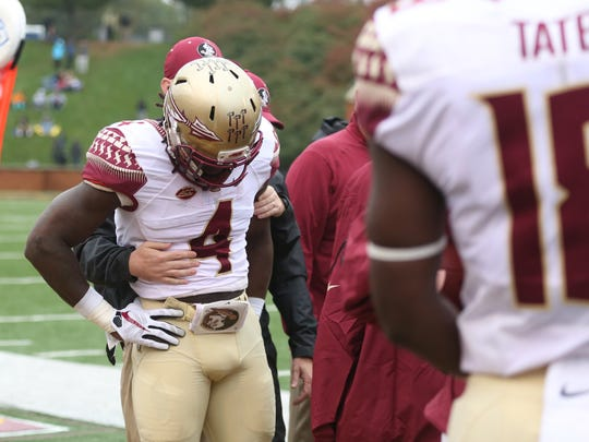 Dalvin Cook is held on the sideline after coming up lame and holding the back of his leg on a play against Wake Forest on Saturday at BB&T Field.