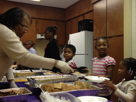 Glenda Pugh, left, helps serve Thanksgiving dinner at the Allenton Heights Boys and Girls Club on Sunday.
