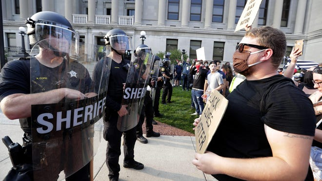 A protester confronts police, Monday, Aug. 24, 2020, in Kenosha, Wis., in response to the shooting of Jacob Blake by a Kenosha police officer a day earlier. COVID-19 has become the leading cause of death of police officers in the U.S. just as a spotlight is shining on the violent deaths of Black people at the hands of officers.
