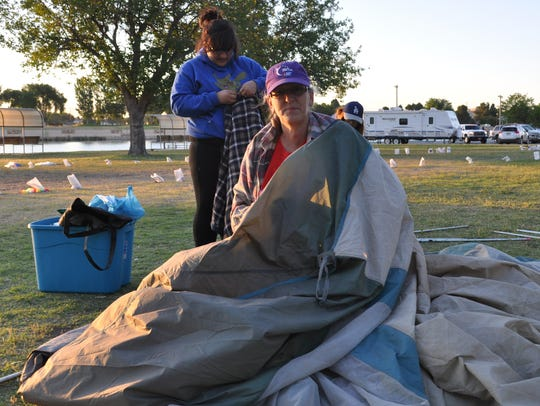 Missy Bowie works on folding up her tent following