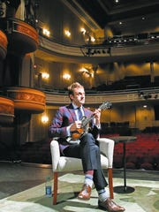Chris Thile plays his mandolin on the stage of the