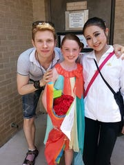 Rieko Hatato (right) poses with dance partner Ilya Artamonov (left) and Olivia Claire Williford, a member of Hatato's ambassador family, during the 2014 USA International Ballet Competition in Jackson.