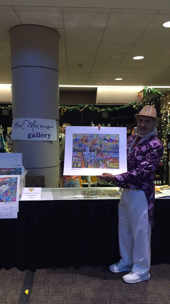El Paso artist Hal Marcus holds up one of his prints