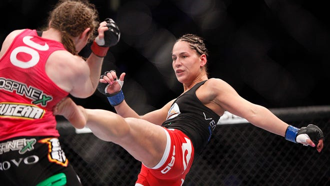 Sarah Kaufman, left, tries to avoid a kick by   Jessica Eye in their women's bantamweight bout at UFC 166 in October. Eye won but had her win taken away due to a positive test for a banned substance.