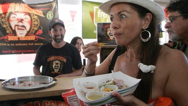 DAVID YAMAMOTO/SPECIAL TO THE STAR Maria Kemp reacts to a mouthful of hot salsa made by Matthew Sisson (back), owner of Ghost Scream, during last year's Salsa Festival.