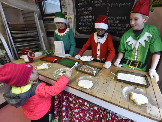 Haddie Schartner of Sturgeon Bay decorates a sugar cookie with help from volunteer elves James Rericha, Wyatt Beaudot and Ty Johnson, from left, at Pink Bakery in Egg Harbor during the village's Holly Days celebration.