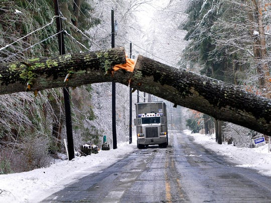A tractor-trailer waits for a tree to be removed from Pa. 233 South in Fayetteville, Pa., Wednesday, Feb. 5, 2014. Another winter storm brought ice an snow to the region. Many trees and wires fell victim to the storm.  (AP Photo/Public Opinion, Markell DeLoatch)