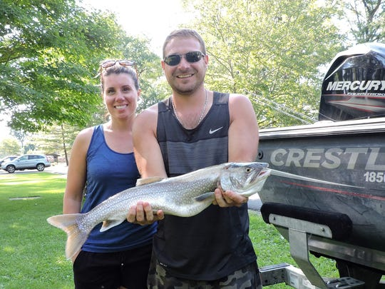 Katie and Brian Mills show off one of the two lake trout they caught Sunday morning with local fishing guide John Gaulke.
