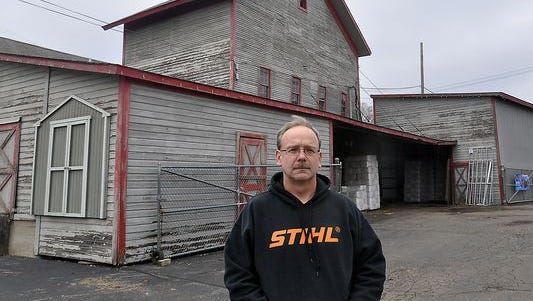 Shawn Shull, manager of Peter's True Value Hardware in South Lyon, stands in front of the old grain elevator on the property next to the railroads tracks.