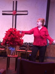 """Actress Terri Swanson admires a poinsettia during Aumsville Community Theatre's production of """"Uh-Oh, Here Comes Christmas."""""""