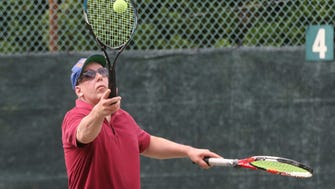 Dr. Don Mueller demonstrates how he serves with two racquets. Throwing the ball up with the racquet in his right hand and serving the ball with his left.