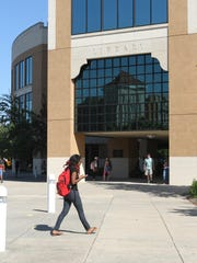 A student walks in front of the library at the University of Louisiana at Monroe.