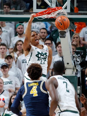 Miles Bridges dunks past Michigan's Isaiah Livers during the first half Saturday in East Lansing.