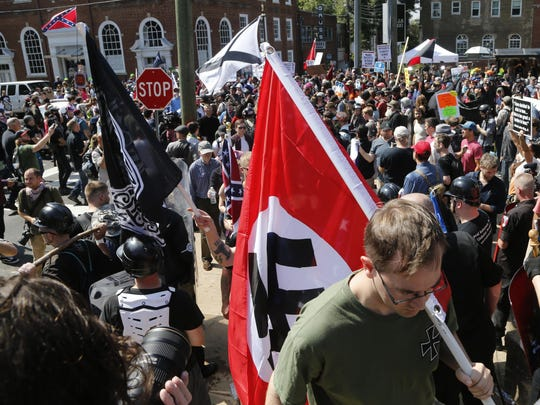 A white supremacist carries a Nazi flag into the entrance to Emancipation Park in Charlottesville, Va., on Aug. 12.