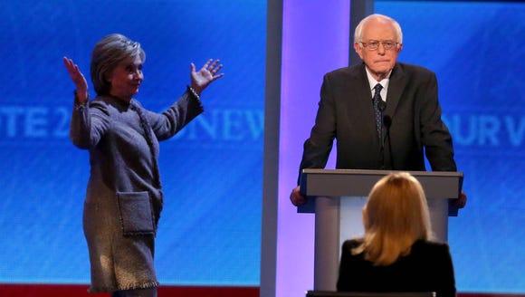 Bernie Sanders waits as Hillary Clinton walks on stage