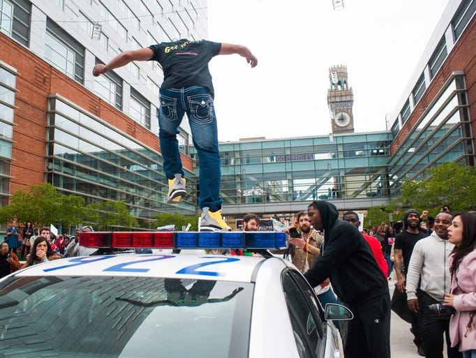 A man jumps on a Baltimore Police car in front of Camden